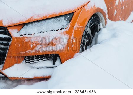 Orange Car Stands On Parking Lot, Covered With White Snow, Stuck After Heavy Snowfall In City. Seaso