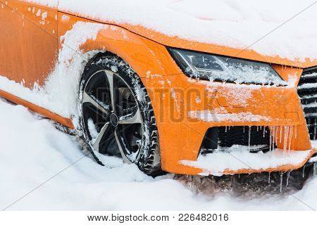 View Of Orange Car Covered With Snow, Stands On Road, Frozen On Frost. Winter And Transportation Con