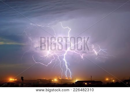 A Massive Electrical Storm Hovering Over A Power Plant In Arlington Arizona During The Monsoon Seaso