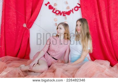 Two Cute Long-haired Girlfriends In Dresses Sit And Cuddle Against