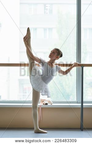 Ballerina Teenager Stretching Leg At Ballet Barre. Beautiful Ballerina In White Ballet Costume Lifti