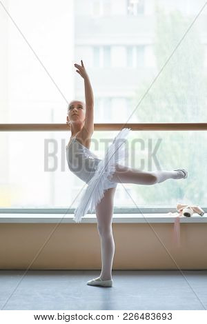 Young Ballerina Practicing Dance Move. Cute Ballet Girl In White Tutu Standing In Ballet Pose In Dan