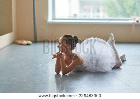 Adorable Ballerina Lying On The Floor. Beautiful Young Ballet Girl In White Tutu Posing On The Floor