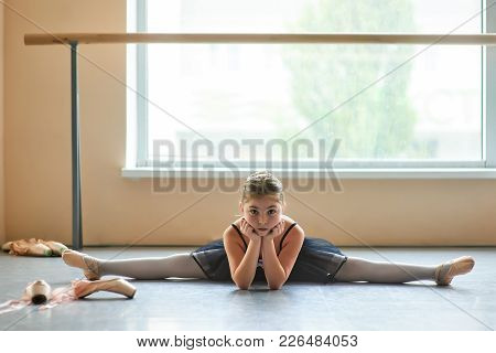 Confident Young Ballerina Doing Leg Split. Pretty Young Ballet Girl Doing The Split In Ballet Class.