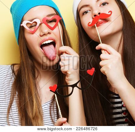 two stylish hipster girls best friends ready for party, over yellow  background