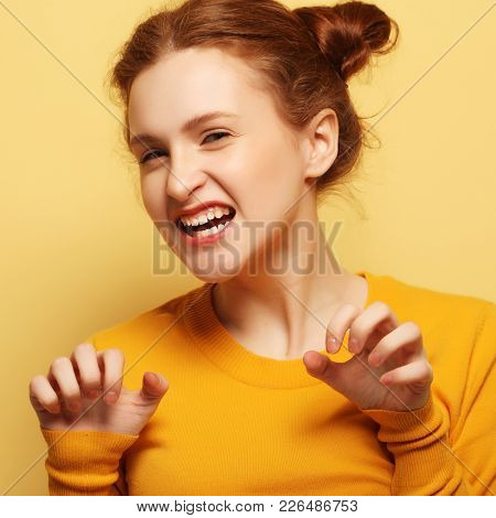 frowning young redhair woman thinking on yellow  background