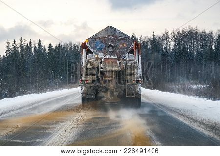 Snowplow On The Highway Throws Sand And Salt