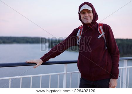 Tourist with backpack on a deck of cruise ship