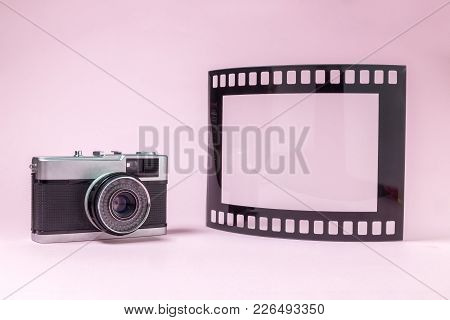 Retro Vintage Camera And Blank Frame In Photo Film Shape Against Pastel Pink Background Minimal Conc