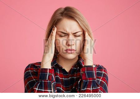 Depressed Stressful Female Has Headache, Keeps Hands On Temples, Closes Eyes As Feel Terrible Pain,