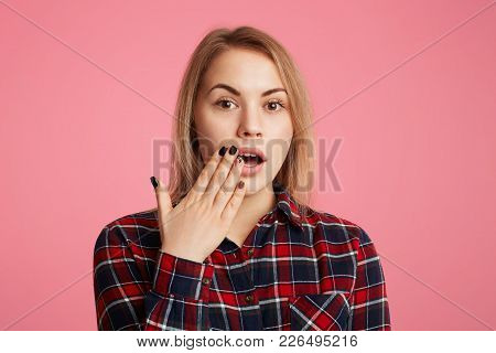 Amazed Female With Opened Mouth, Covers It With Hand, Being Shocked To Watch Something Awful On Tele