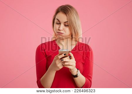 Attractive Female Blows Cheeks As Being Tired Of Messaging On Smart Phone, Can`t Understand Content