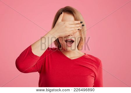 Pretty Female Covers Her Face With Hand, Opens Mouth, Tries To Hide From Someone, Dressed In Casual
