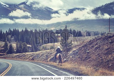 Vintage Toned Picture Of A Female Horse Rider In A Cowboy Hat On A Road, Usa.
