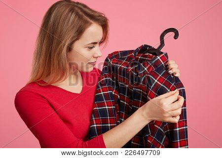 Sideways Portrait Of Pleasant Looking Young Female Chooses New Outfit, Looks On Checkered Chemise On