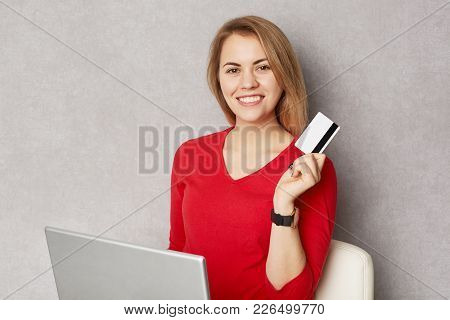 Happy Female Glad To Do Shopping Online, Buys All Necessary Products At Home, Uses Laptop Computer A