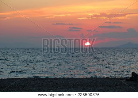 The Sun Sets Over The Mountains Of The Balkan Peninsula In The Aegean Sea.