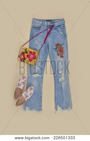 Embroidered flowers jeans, handbag ,shoes on - beige background