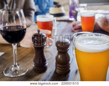 Backlit Glasses Of Beers And A Red Wine On A Dinning Table, With Guests Hands In Waiting. Front Ambe