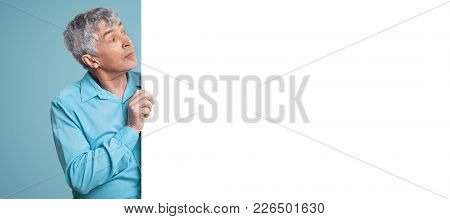 Attractive Grey Haired Male In Blue Formal Shirt Stands Aside Looks At Blank White Copy Space For Yo