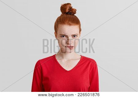 Dissatisfied Pleasant Looking Ginger Woman With Hair Knot Curves Lips In Dissatisfaction, Has Grumpy