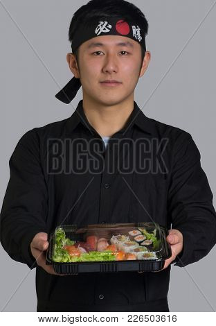 Asian cook holding take away sushi set on plastic container and wearing a black bandana in Chinese word translation ( Victory )