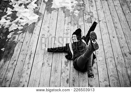 Young Girl Wear On Long Green Sweatshirt, Jeans And Black Headwear Sitting On Wooden Floor With Snow