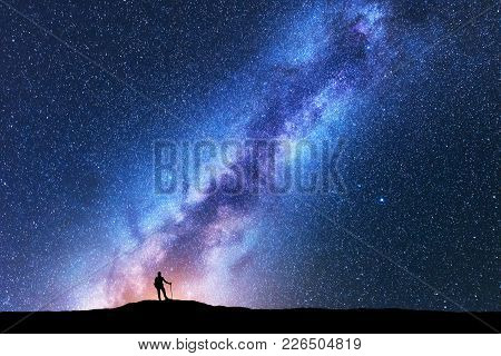 Silhouette Of Man With Trekking Poles Against Amazing Milky Way At Night. Space Background. Landscap