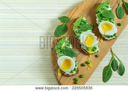 Freshly Cooked Toasts With Cottage Cheese And Herbs, Green Peas, Soft Egg And Spinach. Concept Of He