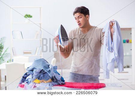 Inattentive husband burning clothing while ironing