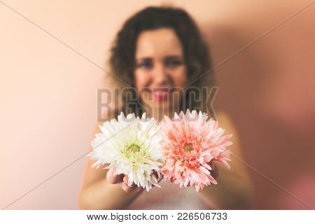 Beautiful Curly Young Woman Holding Two Flowers, Pink And White On Color Background At Home. Hello S