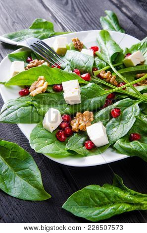 Spinach salad with nuts and apples served on table