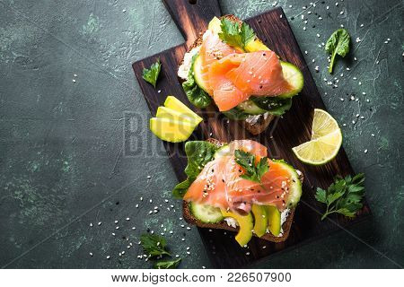 Open Sandwich Or Toast. Grain Bread With Salmon, White Cheese, Avocado, Cucumber And Spinach. Top Vi