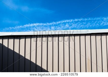 Half Wall With Shadow Half Blue Sky . Top Part Of The Picture Is Blue Sky, Bottom Part Is Pink Wall