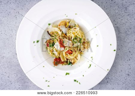 Spaghetti alle vongole with tomato pesto as top view on a plate