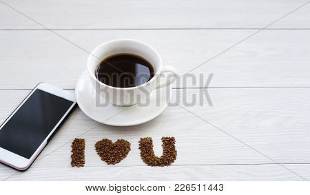 Hot Cup Of Black Instant Coffee With I Love U Letter And Mobile Phone On White Wooden Table With Cop