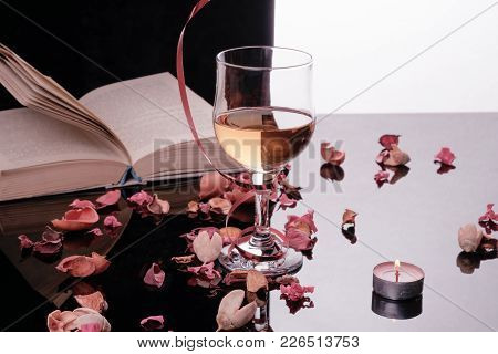 A Glass Of White Wine And Petals. A Glass Of White Wine, Lying Next To Rose Petals. Behind The Glass