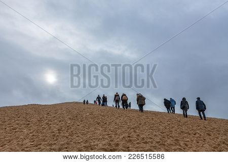 Pilat, France - December 28, 2017: Tourists Climbing The Pilat Dune (dune Du Pilat) During A Cloudy