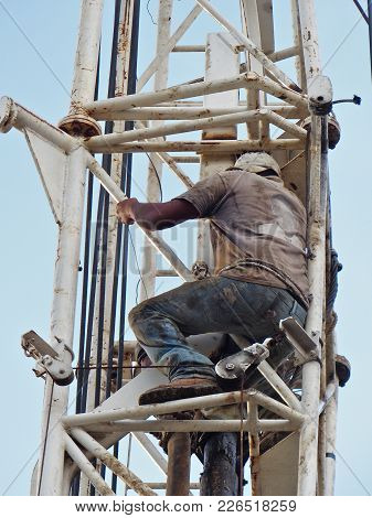 A Worker On A Tower Of A Drilling Machine  Drilling A Water Well In Guatemala Without Safety Equipme