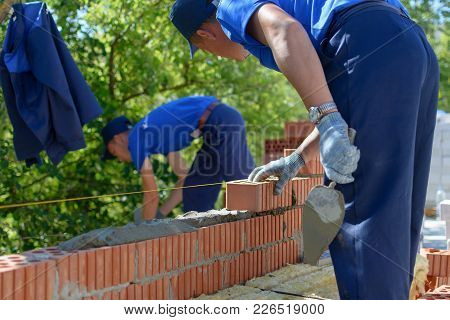 Yoshkar-ola, Russia - June 8, 2015 Construction Mason Worker Bricklayer Making A Brickwork With Trow