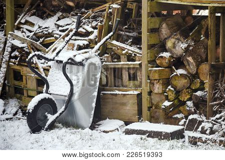 Firewood Logs And A Wheelbarrow In An Old Wooden Shed In The Snow, Cheap Heating In Winter