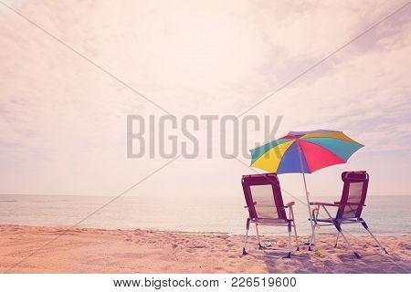 Retro Style Picture Of Seaside With Two Deck Chairs Under A Multicolored Sun Umbrella