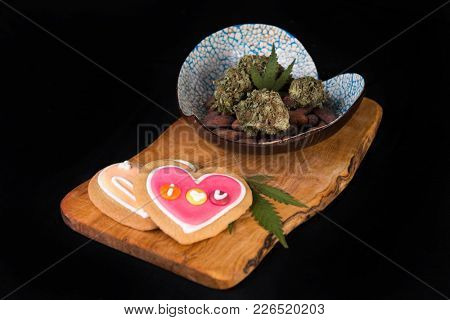 Dried cannabis nugs with cacao beans and baked cookies on a tray - infused marijuana edibles concept