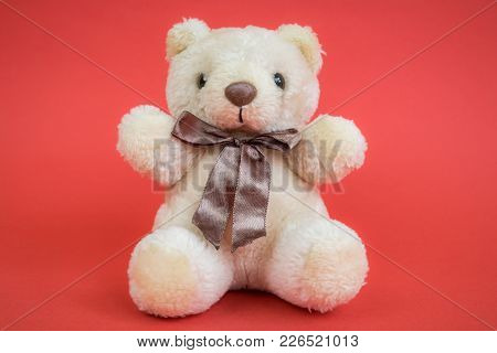 Soft Toy Teddy Bear, Pale Brown Or Beige, With Silky Bow, On The Red Background. Childhood Concept.