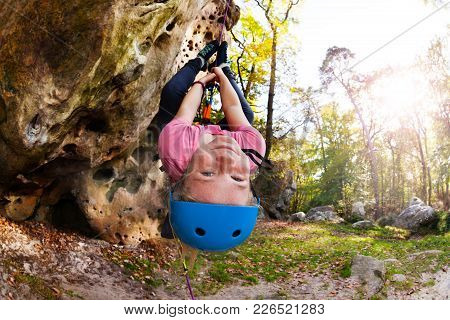 Cute Girl In Helmet Hanging Upside-down During Rock Climbing Train Outdoors In Forest Area