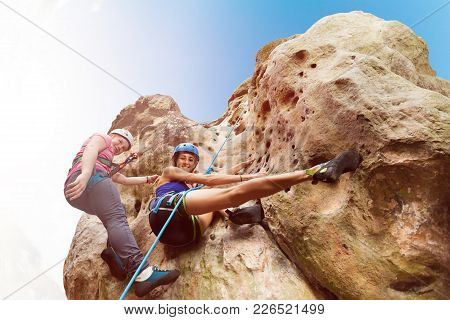 Bottom View Portrait Of Female Instructor Teaching Teenage Girl Climbing A Rock With Harnesses Again