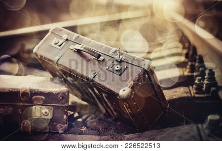 Two Old Vintage Suitcases Lie On Railway Rails.