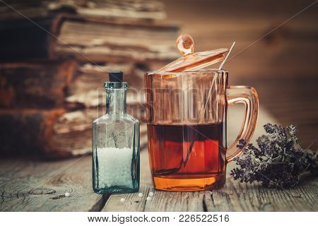 Tincture Or Healthy Tea In Glass, Vial Of Homeopathic Globules, Old Books And Bunch Of Dry Healthy H