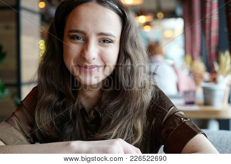 Portrait Of A Young Girl In A Brown Blouse In A Cafe. Beautiful Girl Is Sitting In A Cafe. Big Brown