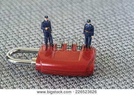 Miniature Figure Security Guards Standing On Red Combination Pad Lock With The Background Of Compute